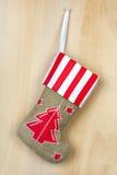 Botte rouge de Noël avec des cadeaux sur le mur en bois Photo stock