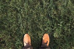 Bottes beiges de suède sur une herbe verte Vue supérieure, configuration plate Image stock