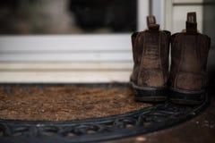 Bottes d'agriculteurs laissées par la porte Images stock