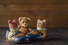 Bottes de bébé et poupée de jouet sur la table en bois Photos libres de droits