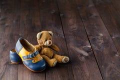 Bottes de bébé sur la table en bois au-dessus du fond grunge de mur, vintage Photo libre de droits