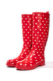 Bottes de caoutchouc rouges et blanches de point de polka faisant face sous un angle de côté images libres de droits