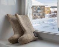 Bottes de feutre sur le rebord de fenêtre Paysage rural d'hiver en dehors de photos stock