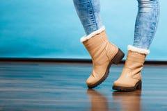 Bottes de fourrure d'hiver sur les pieds femelles photo stock