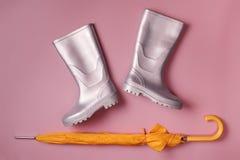Bottes de parapluie et de pluie sur le rose Photo libre de droits