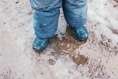 Bottes de pluie d'enfant dehors dans l'action photographie stock