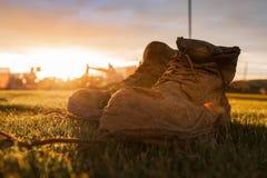 Bottes de sécurité à un chantier de construction couvert dans la boue devant un coucher du soleil lumineux images libres de droits
