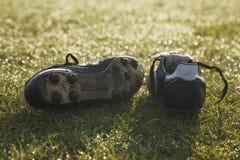 Bottes du football sur un terrain de football vide Photos stock