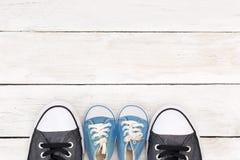 Bottes du ` s de papa et espadrilles du ` s de bébé, sur le fond en bois blanc, f Images libres de droits
