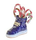 Bottes en céramique bleues, espadrilles, avec Noël, sucreries de vacances, bonbons, fin, fond d'isolement et blanc Photo stock