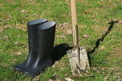 Bottes en caoutchouc noires et pelle sale avec l'herbe verte au printemps image libre de droits