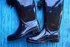 Bottes en caoutchouc noires sur une table en bois bleue Photos stock