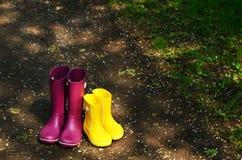 Bottes en caoutchouc pour la femme et l'enfant dans le jardin Image libre de droits