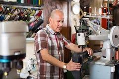 Bottes en cuir de couture d'ouvrier mûr sur le tour de point Photographie stock
