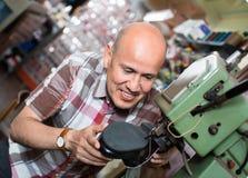 Bottes en cuir de couture d'ouvrier mûr sur le tour de point Photo stock
