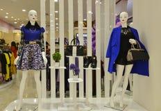 Bottes en cuir et mannequin femelle avec le sac à main dans une fenêtre de boutique de mode Photographie stock