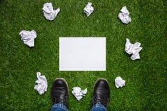 Bottes et feuille de papier avec les feuilles cramled sur l'herbe Images stock