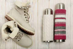 Bottes légères d'hiver et un thermos dans la couverture tricotée sur le bri Photos stock