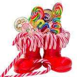Bottes rouges de Santa Claus, chaussures avec les lucettes douces colorées, candys Botte de Saint-Nicolas avec des cadeaux de pré Images stock