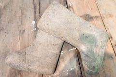 Bottes sales et utilisées de feutre sur un plancher en bois Chaussures russes traditionnelles d'hiver de Valenki dans la campagne images libres de droits