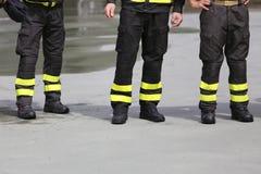 Bottes uniformes des sapeurs-pompiers dans la bouche d'incendie image stock