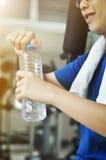 Bottiglia asiatica della tenuta della donna di acqua dopo l'allenamento Fotografie Stock