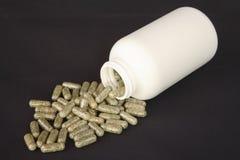 Bottiglia bianca che rovescia le capsule dell'erba Fotografia Stock Libera da Diritti