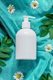 Bottiglia bianca con il cosmetico sul fondo di seta verde del panno con i fiori e le foglie del campo Il concetto di estate e del Immagini Stock