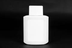 Bottiglia bianca con l'etichetta in bianco su fondo scuro immagini stock