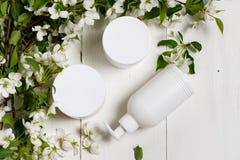 Bottiglia bianca dei cosmetici di cura del corpo con i fiori posti pianamente fotografia stock libera da diritti