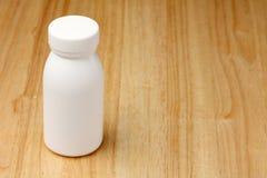 Bottiglia bianca sulla tavola di legno Fotografia Stock Libera da Diritti