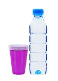 Bottiglia blu con le tazze della plastica e dell'acqua isolate Fotografie Stock Libere da Diritti