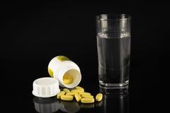 Bottiglia capovolta di medicina e di bicchiere d'acqua Immagini Stock Libere da Diritti