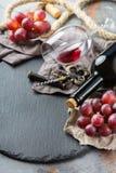 Bottiglia, cavaturaccioli, vetro di vino rosso, uva su una tavola Fotografia Stock