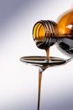 Bottiglia che versa un liquido su un cucchiaio Su una priorità bassa bianca Farmacia e fondo sano medicina Tosse e droga fredda Immagine Stock