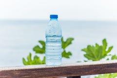 Bottiglia con acqua potabile pulita contro il mare Immagini Stock Libere da Diritti