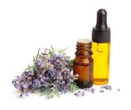 Bottiglia con i fiori del petrolio e della lavanda dell'aroma isolati su fondo bianco fotografia stock