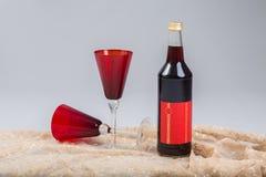 Bottiglia con i vetri rossi Immagini Stock