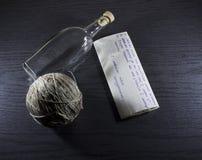 Bottiglia con il messaggio su uno scrittorio di legno Immagini Stock Libere da Diritti