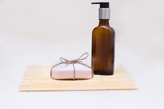 Bottiglia con l'erogatore e un pezzo di sapone rosa su una tavola bianca Fotografie Stock Libere da Diritti