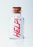 Bottiglia con un aiuto del messaggio! Fotografia Stock
