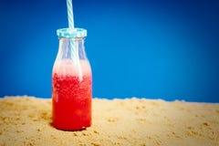 Bottiglia con un cocktail delizioso dell'anguria sulla sabbia Fotografia Stock Libera da Diritti