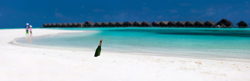 Bottiglia con un messaggio alla spiaggia tropicale Fotografia Stock