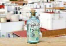 Bottiglia con un segno da cinque libbre dentro Immagine Stock