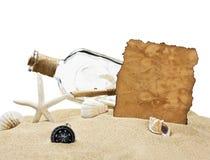 Bottiglia con una nota e una bussola Fotografie Stock