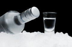 Bottiglia con vetro di vodka che si trova sul ghiaccio su fondo nero Fotografia Stock