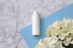 Bottiglia cosmetica con i fiori su fondo di marmo Disposizione piana Bio- concetto di prodotto del prodotto biologico immagini stock