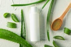 Bottiglia crema con spazio per testo, il cucchiaio di legno, le fette di vera dell'aloe e le foglie sulla tavola bianca, vista su immagini stock libere da diritti