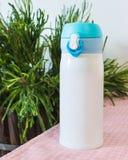 Bottiglia d'acciaio blu sul fondo del tavolo da cucina Contenitore in bianco della bevanda per progettazione fotografie stock