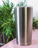 Bottiglia d'acciaio sul fondo del tavolo da cucina Tazza in bianco della bevanda per progettazione fotografie stock